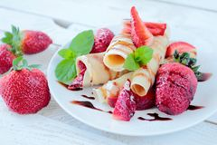 Sweet pancakes with strawberries and chocolate sauce Royalty Free Stock Photos