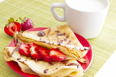 Sweet pancakes with strawberry and cup of milk. On white background royalty free stock image