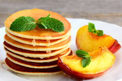Sweet pancakes with syrup and grilled nectarines on a white plate. Homemade sweet pancake recipe. Delicious breakfast or brunch. Sweet pancakes. Sweet pancakes Stock Photography