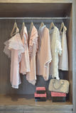 Sweet pastel blouses are hanging in open wardrobe. Sweet pastel blouses are hanging in open wooden wardrobe stock photos