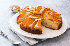 Sweet peach cake. Sweet homemade  peach cake served on a white plate over gray stone background Stock Photo