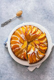 Sweet peach cake. Sweet homemade  peach cake served on a white plate over gray stone background. Top view Stock Image