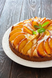 Sweet peach cake. Sweet homemade  peach cake served on a white plate over old wood background Royalty Free Stock Photo
