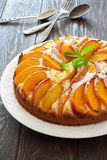 Sweet peach cake. Sweet homemade  peach cake served on a white plate over old wood background Stock Photography