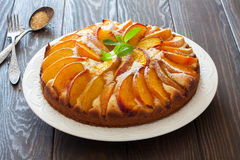 Sweet peach cake. Sweet homemade  peach cake served on a white plate over old wood background Stock Images