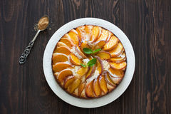 Sweet peach cake. Sweet homemade  peach cake served on a white plate over old wood background.Top view Royalty Free Stock Image