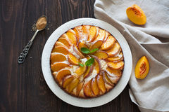 Sweet peach cake. Sweet homemade peach cake served on a white plate over old wood background.Top view royalty free stock images