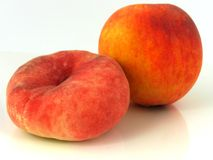 Sweet Peaches. The Donut Peach depicted here along side a regular peach is a descendant of the flat peaches of China.  Up to 3 1/2 inches in diameter, it is flat Stock Photo