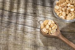 Toasted peanuts on wooden background - Arachis hypogaea stock photography