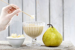 Sweet pear fondue on wooden table Stock Images