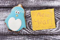 Sweet penguin with New Year`s greetings. Bright figure of a penguin gingerbread. Children`s winter card stock photography