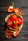 Sweet pepper in a basket and pieces of fresh pepper. On wooden background royalty free stock photography