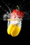 Sweet pepper drop into water. On black background Royalty Free Stock Image