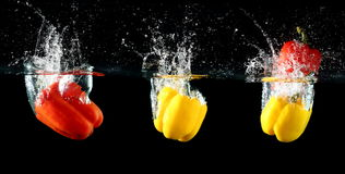 Sweet pepper drop into water. On black background Stock Photography