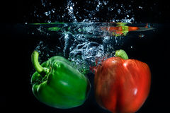 Sweet pepper drop into water on black background. Sweet pepper and broccoli drop into water on black background Royalty Free Stock Images