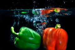 Sweet pepper drop into water on black background. Sweet pepper and broccoli drop into water on black background Stock Images