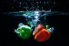 Sweet pepper drop into water on black background. Sweet pepper and broccoli drop into water on black background Royalty Free Stock Photos