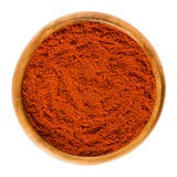 Sweet pepper red paprika powder in wooden bowl over white. Sweet pepper red paprika powder in wooden bowl. Ground spice made from air-dried and smoked bell Stock Photos