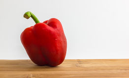 Sweet pepper. Red sweet pepper on wooden cutting board and white background Royalty Free Stock Photos