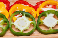 Sweet pepper slices. Sliced red yellow and green sweet peppers (capsicum) laying on a kitchen cutting board Stock Photography