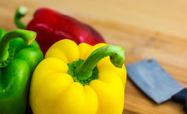 Sweet pepper. Three sweet peppers and kinfe on a wooden background Royalty Free Stock Image