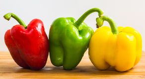Sweet pepper. Three sweet peppers on a wooden and white background Royalty Free Stock Photos