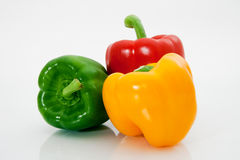 Sweet peppers. Red, yellow and green sweet peppers macro on a white background Royalty Free Stock Images