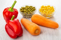 Sweet peppers, carrots, green peas and corn in bowls on table stock photo