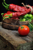 Sweet peppers, chili peppers in a wooden bowl. Together with a tomato on a wooden desk Royalty Free Stock Photos