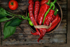 Sweet peppers, chili peppers in a wooden bowl. Together with a tomato on a wooden desk Royalty Free Stock Images