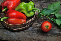 Sweet peppers, chili peppers in a wooden bowl. Together with a tomato on a wooden desk Royalty Free Stock Photography
