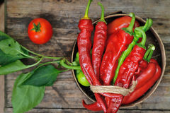 Sweet peppers, chili peppers in a wooden bowl. Together with a tomato on a wooden desk Stock Photography