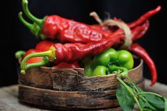 Sweet peppers, chili peppers in a wooden bowl. Together with a tomato on a wooden desk Stock Image