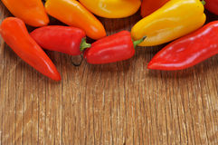 Sweet peppers of different colors on a rustic table. Some sweet peppers of different colors, orange, red and yellow, on a rustic wooden table Royalty Free Stock Photos