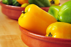 Sweet peppers of different colors. Some sweet peppers of different colors, orange, red and yellow, in an earthenware bowl Royalty Free Stock Image