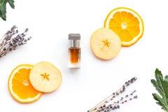 Sweet perfume with fruit fragrance. Bottle of perfume near apple, orange, lavender, cinnamon on white background to. Sweet perfume with fruit fragrance. Bottle royalty free stock image