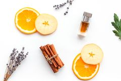 Sweet perfume with fruit fragrance. Bottle of perfume near apple, orange, lavender, cinnamon on white background to. Sweet perfume with fruit fragrance. Bottle stock photos