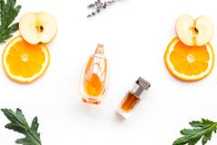 Sweet perfume with fruit fragrance. Bottle of perfume near apple, orange, lavender on white background top view.  royalty free stock photo