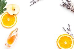 Sweet perfume with fruit fragrance. Bottle of perfume near apple, orange, lavender on white background top view cop. Sweet perfume with fruit fragrance. Bottle stock images