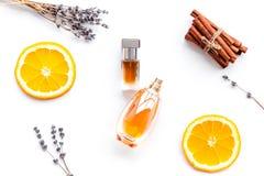 Sweet perfume with fruit fragrance. Bottle of perfume near orange, lavender, cinnamon on white background top view.  stock photos