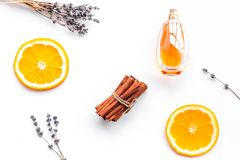Sweet perfume with fruit fragrance. Bottle of perfume near orange, lavender, cinnamon on white background top view.  stock images
