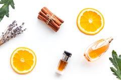 Sweet perfume with fruit fragrance. Bottle of perfume near orange, lavender, cinnamon on white background top view. Sweet perfume with fruit fragrance. Bottle of stock photography
