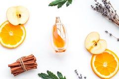 Sweet perfume with fruit fragrance. Bottle of perfume near apple, orange, lavender, cinnamon on white background to. Sweet perfume with fruit fragrance. Bottle stock photography