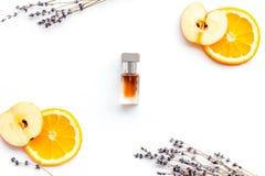 Sweet perfume with fruit fragrance. Bottle of perfume near apple, orange, lavender on white background top view.  stock photos