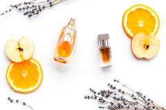 Sweet perfume with fruit fragrance. Bottle of perfume near apple, orange, lavender on white background top view.  stock images