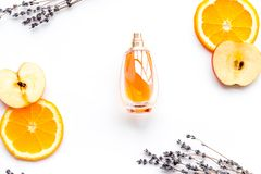 Sweet perfume with fruit fragrance. Bottle of perfume near apple, orange, lavender on white background top view.  stock photography
