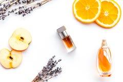 Sweet perfume with fruit fragrance. Bottle of perfume near apple, orange, lavender on white background top view.  royalty free stock photos