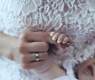 Sweet photo of cute baby hand in mom hands. Tender interior photo of cute baby hand in mom hands stock photo