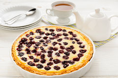 Sweet pie baked with frozen cherries on wooden table. Royalty Free Stock Image