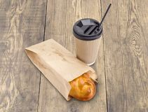 Pie in brown paper bag and tea in paper cup. Sweet pie in the fast food brown paper bag and tea in the disposable insulated paper cup with plastic lid and Stock Photo
